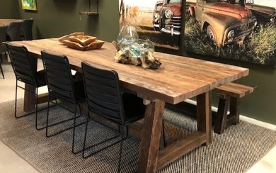 Dining table with a bench made from recycled planks from houses.