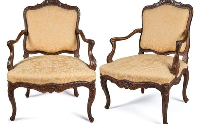 TWO FAUTEUILS with QUEEN REGENCE and LOUIS XV in moulded and richly carved natural wood, the backrests decorated with the cushioning of a flower. The moved armrests, one with a cuff, ending in scrolls with water and acanthus leaves that extend on...