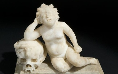 A 18th century alabaster group of Cupid on a skull