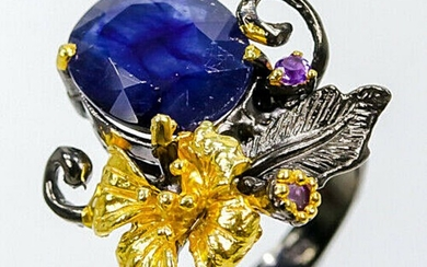 A sapphire and amethyst ring set with an oval-cut sapphire and smaller circular-cut amethysts, mounted in black rhodium and gold plated sterling silver.