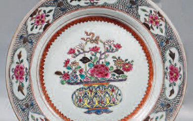 China porcelain soup plate. Qianlong, 18th century. With Rose Family enamels decoration, in the center of a basket decorated with flowers in a medallion formed by a frieze of palmettes, flowers in four-lobed reserves standing out on a vermiculated...