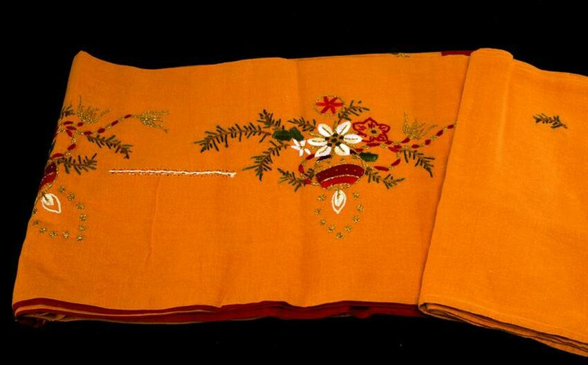 Linen tablecloth in orange with Christmas motifs.