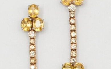 Pair of white gold earrings, each adorned with a line of brilliant-cut diamonds ending in yellow sapphires. Length: 4cm. Weight: 7g.