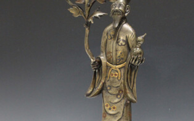 A Chinese mixed metal inlaid bronze sectional figure of an immortal on stand, late Qing dynasty, the