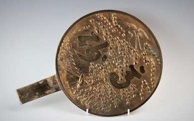 A Japanese bronze hand mirror, of circular form, decorated w...