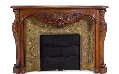 A Louis XV Style Carved Walnut and Pressed Gilt Metal Fireplace