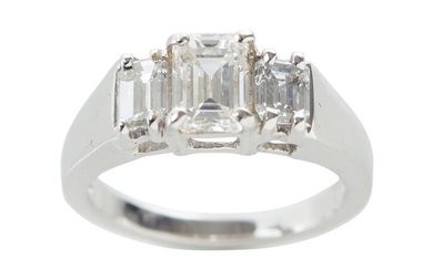 A THREE STONE DIAMOND RING IN 18CT WHITE GOLD, CENTRALLY SET WITH AN EMERALD CUT DIAMOND OF 1.30CTS FLANKED BY FURTHER EMERALD CUT D...