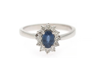 A sapphire and diamond ring set with a sapphire encircled by numerous diamonds, mounted in 14k white gold. Size 55.