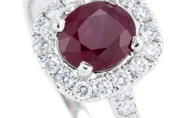 AN 18CT WHITE GOLD RUBY AND DIAMOND CLUSTER RING; centring an oval cut ruby of approx. 0.85ct to surround and shoulders set with 30...
