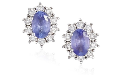 A PAIR OF TANZANITE EARSTUDS, each oval-shaped tanzanite...