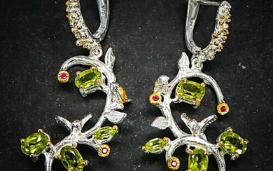 A pair of peridot and garnet ear pendants each set with numerous oval, navette and circular-cut peridots and rhodolite garnets, mounted in rhodium plated silver