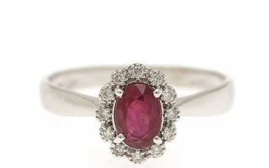 A ruby and diamond ring set with an oval-cut ruby encircled by numerous brilliant-cut diamonds, mounted in 18k white gold. Size 55.