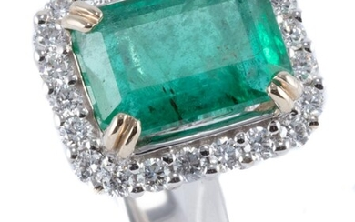 AN 18CT GOLD EMERALD AND DIAMOND RING; corner claw set with an emerald cut emerald of approx. 3.18ct surrounded by 22 round brillian...