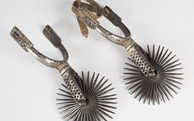 Pair of wrought iron spurs with silver damasking.