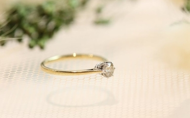 Solitaire ring in yellow and white gold holding...