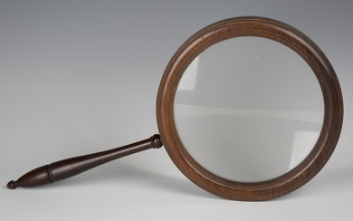 A 19th century rosewood gallery glass, the large circular frame supporting a glass lens, length 45.5