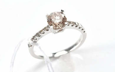 A SOLITAIRE DIAMOND RING - Featuring a round brilliant cut champagne diamond weighing 1.02ct to a diamond set band featuring twelve...