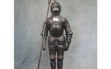 A cast iron figure of a knight in armour carrying a halberd,...