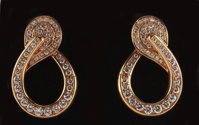 A pair of yellow gold diamond scroll earrings, each set with...