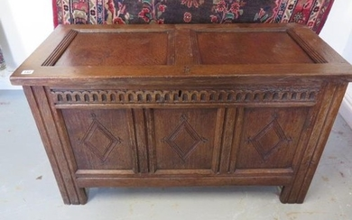 An 18th century oak coffer with a carved three panel front, ...