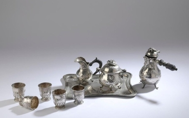 Silver coffee service decorated in repoussé with lion mufles and garlands of flowers including: a coffee pot, a covered sugar bowl, a creamer, a rectangular tray.