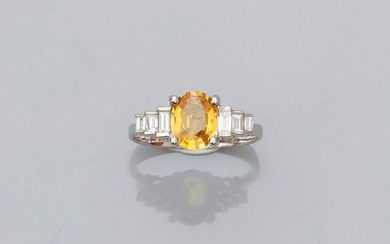 White gold ring, 750 MM, set with an oval yellow sapphire weighing 1.55 carat and set with six stepped baguette-cut diamonds, 17 x 9 mm, size: 55, weight: 3.5gr. rough.