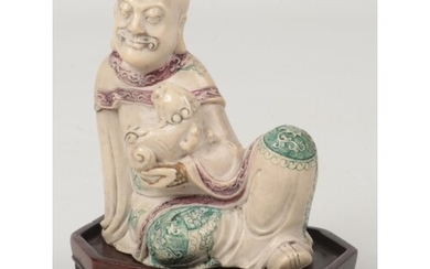 A 19th century Chinese carved soapstone figure raised on a c...