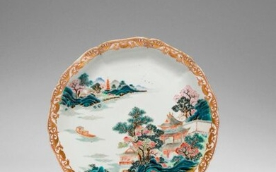 A CHINESE FAMILLE ROSE MOULDED 'LANDSCAPE' DISH QIANLONG 1736-95 Painted with pagodas and buildings by a river amongst colourful leafy trees, with a sampan on the water, decorated in iron-red and gilt with a continuous peony scroll encircling the...