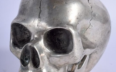 A SILVER PLATED SCULPTURE OF A SKULL. 10.5 cm x 12 cm.