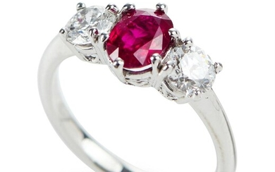 A THREE STONE RUBY AND DIAMOND RING IN 18CT WHITE GOLD, FEATURING AN OVAL CUT RUBY OF 1.10CTS, SHOULDERED BY ROUND BRILLIANT CUT DIA...