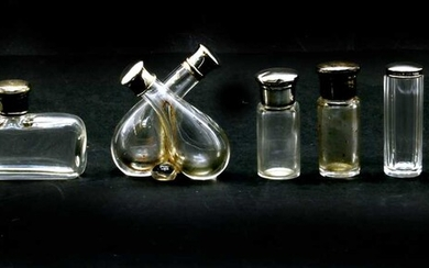 A collection of silver lidded glass scent and drawing table jars