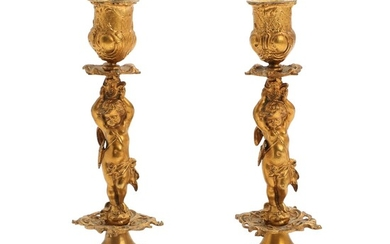 NOT SOLD. A pair of French late 19th century gilt bronze candlesticks, cast with putti...
