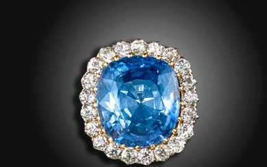 A sapphire and diamond cluster ring, the cushion-shaped sapphire weighs approximately 38.00cts, set within a surround of old circular-cut diamonds in platinum and gold, diamonds approximately 3.00cts total, size X Accompanied by report number 80274-59...