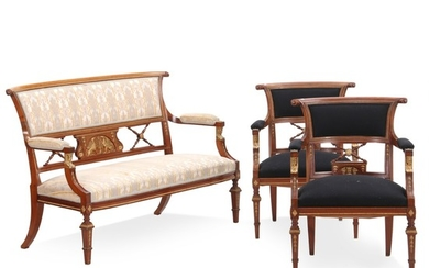 An Empire style suite of mahogany furniture, consisting of a settee and a pair of armchairs. Gilt bronze ornaments. Early 20th century. (3).