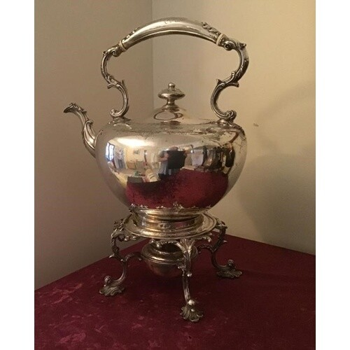 Large solid silver kettle standing on a 4 legged stand with ...