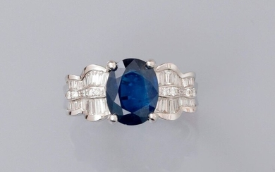 Ring in white gold, 750 MM, centered by a beautiful oval sapphire weighing about 3 carats and supported by two movement patterns covered with baguette-cut and brilliant-cut diamonds, total about 0.60 carat, size: 54, weight: 6.85gr. rough.