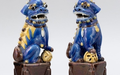 """TWO CHINESE BLUE AND YELLOW GLAZED PORCELAIN FU DOGS Seated with brocade balls on aubergine bases. Heights 8.5""""."""