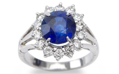 A SAPPHIRE AND DIAMOND RING - Featuring an oval sapphire weighing 4.45cts, within a border of round brilliant cut diamonds totalling...