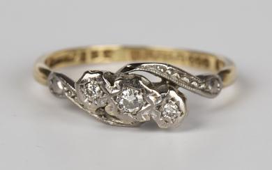 An 18ct gold and diamond three stone ring, mounted with a row of circular cut diamonds in a crossove