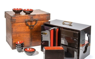 Black lacquered travel Bento lunch box, consisting of trays, alcohol container, chopstick box, plates, and a box containing a set of three bowls with lids and a set of three bowls without lids. Red lacquered inside. Meiji period.