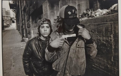 MARK, MARY ELLEN (1941-2015) Seattle, [Rat and Mike with a gun], 1983. Gelatin silver print, 12 1/2 x 18 3/4 inches (320 x...