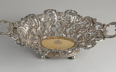 Silver dish, 812/000, openwork oval model with curls and grapevines, placed on 4 ball legs. In the center of the bowl is a gilded element with a weapon engraving with text: Laboris Praemia Recti. 34x23x8cm. ca 381 grams. In good condition
