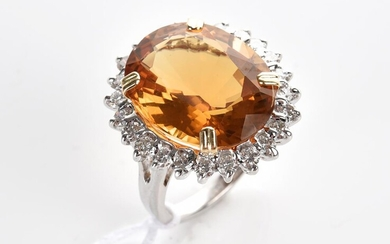 A CITRINE AND DIAMOND COCKTAIL RING IN 18CT TWO TONE GOLD, THE OVAL CUT CITRINE WEIGHING 13CTS, IN A SURROUND OF DIAMONDS TOTALLING...