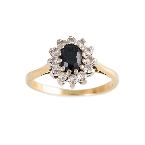 A DIAMOND AND SAPPHIRE CLUSTER RING, the oval sapphire to an...