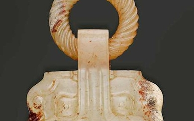 A PALE CELADON AND RUSSET JADE BELT HOOK IN THE SHAPE OF A RINGED TAOTIE-MASK.