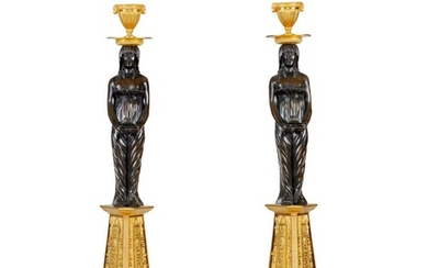 A pair of Directoire patinated and gilt-bronze candlesticks, circa 1800 | Paire de bougeoirs en bronze doré et patiné d'époque Directoire, vers 1800
