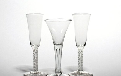 A pair of large wine fluted or ale glasses c.1760, the tall slender bowls raising from double series opaque twist stems, and a large drawn trumpet glass raised on a plain stem enclosing a long tear, 19cm. (3)