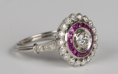 A platinum, diamond and ruby cluster ring, collet set with the principal circular cut diamond within