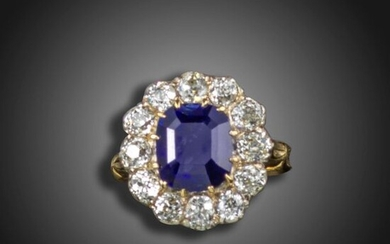 A sapphire and diamond cluster ring, the cushion-shaped sapphire is...