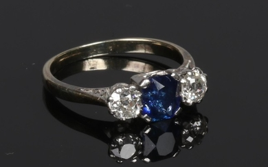 A yellow metal sapphire and diamond three stone ring. The cu...